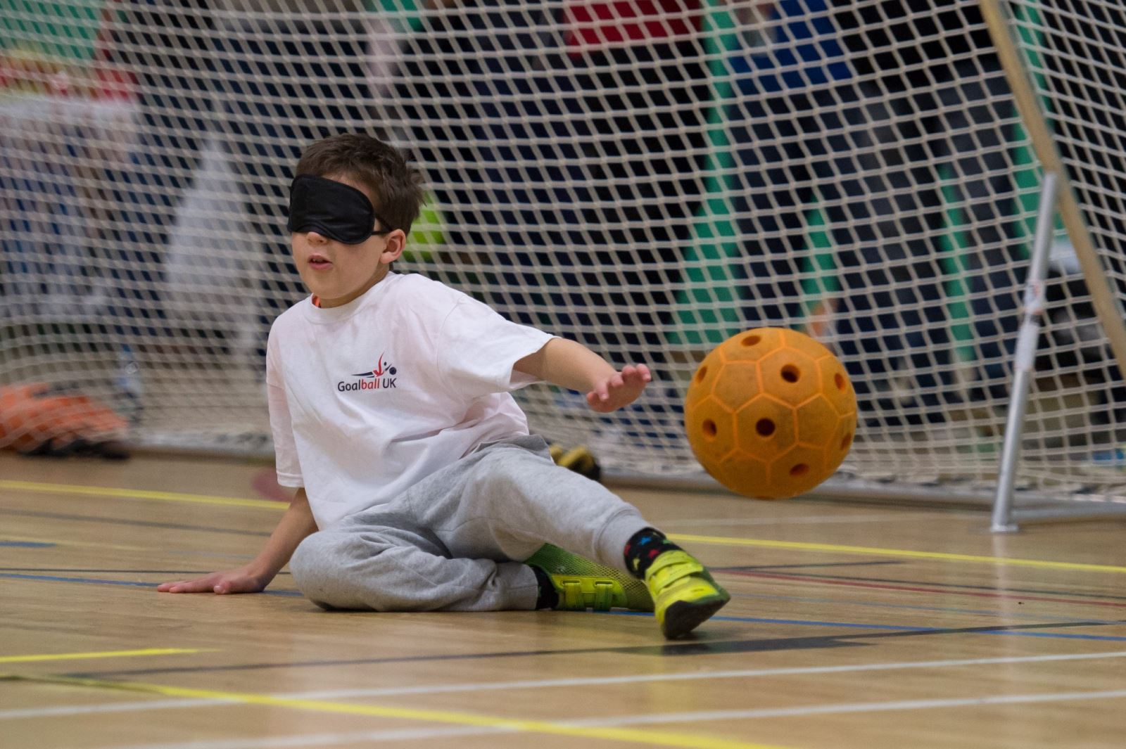Child with eyeshades in front of goal as ball passes him