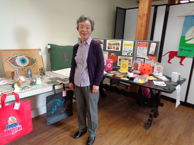 Volunteer in front of craft and information displays